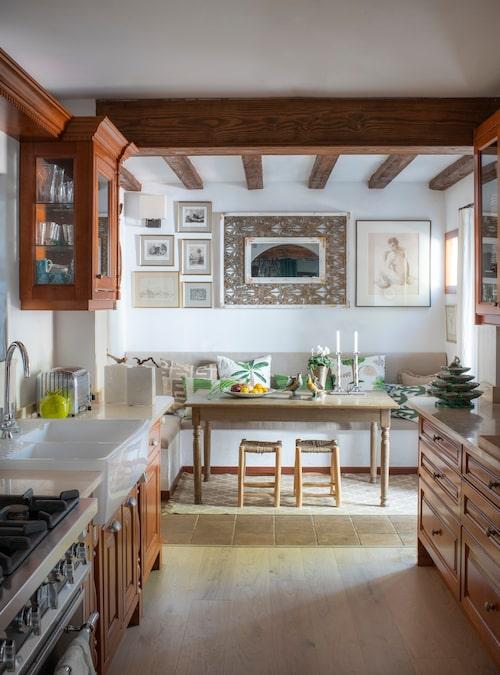 """""""Ingen minimalism här, huset kräver ett kök i spansk, rustik stil."""" Originalinredningen finns kvar, kompletterad med en ny skåpvägg och nya bänkskivor i marmor. Soffan är platsbyggd, tyget är grovt spanskt linne, kuddar från Boussac och Canovas. På bänkarna franska bonbonjärer med fåglar och fransk ostronplatå."""