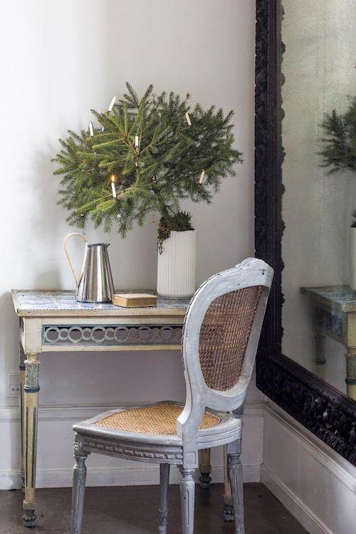 På det antika bordet står en kruka med en liten gran i. Kanna, Stelton och vas, Lyngby porslin. Bord, stol och spegel från trendfirst.com.