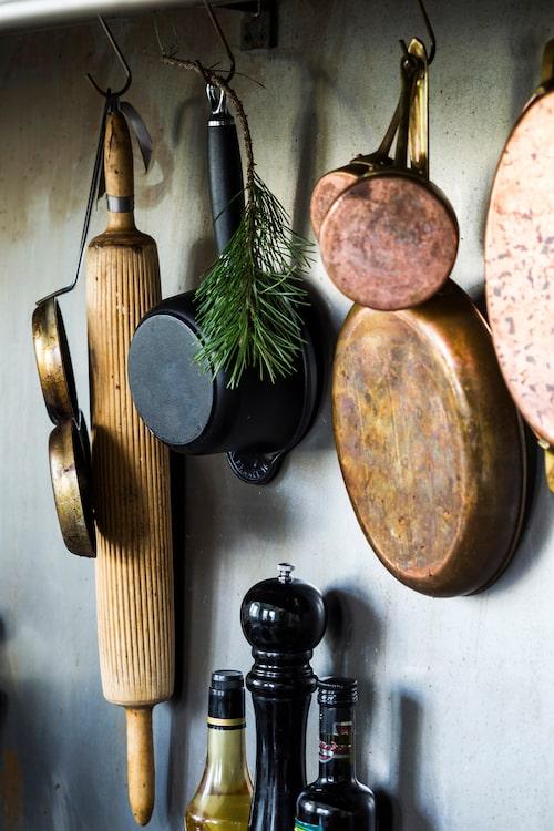 Grytor, stekpannor och köksredskap på rad ovanför spisen. En enkel tallkvist ger doft och julkänsla.