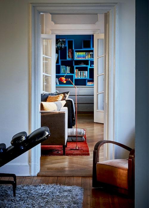 Den blå hyllan är platsbyggd och designad av Laurence. I hörnet står en pampig vintage art deco-fåtölj. Den röda golvlampan ärfrån Lightworks.