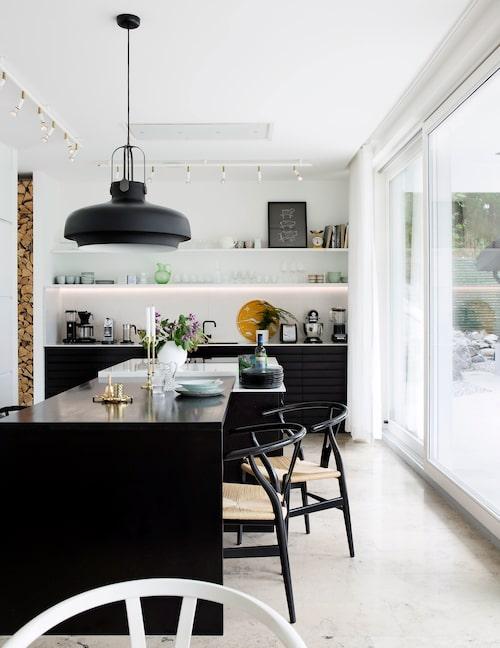 Det luftiga köket är platsbyggt av snickare. Lägg märke till vedförvaringen som anas till vänster. Köksön rymmer både förvaring, matplats och arbetsyta.