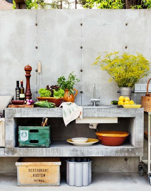 Arbetsbänk och diskplats i betong och med kraftfulla dimensioner. Fransk keramik i kontrast till betongen, och på golvet Signe Persson-Melins planteringskärl Gråsippa i gjutet aluminium från Byarums bruk.