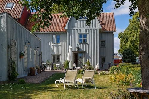 Grått hus med grå knutar och skönt gröna fönster.