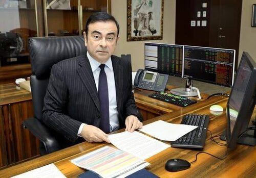 Här sitter Carlos Ghosn och fifflar med papper.