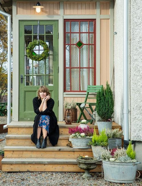 Clara Lidström sitter vid sin älskade punschveranda, som var hennes 30-årspresent till sig själv. Claras klänning kommer från det egna klädmärket Miss Clarity.