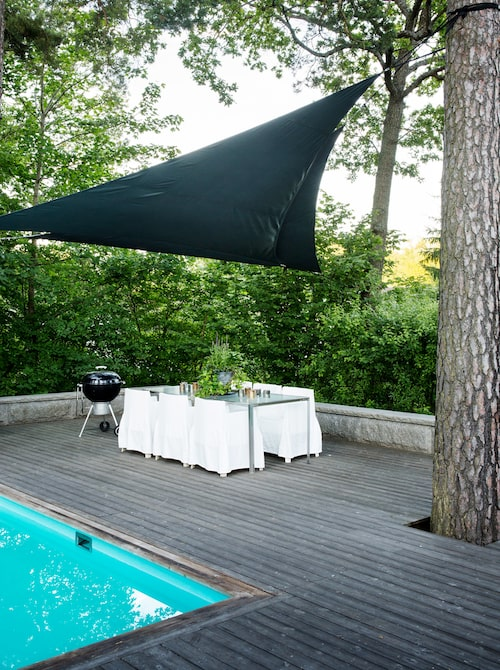 Det stora trädäcket rymmer också en matplats under det stora solskyddet. Matbord från Gervasoni och stolar i design av Philippe Starck för Driade. Grill från Weber
