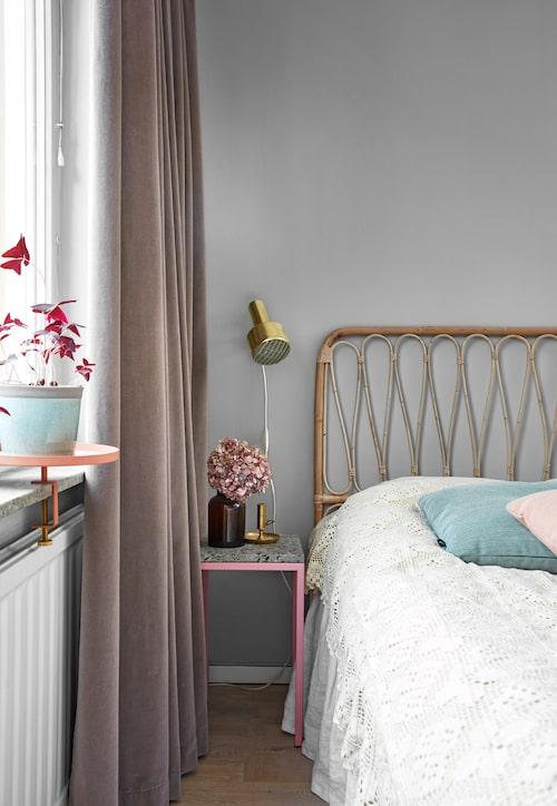 Rart bäddat med virkat överkast. Det och vägg-lampan är loppis-fynd. Sänggaveln är från Tiretta living. Sängbord, Reis Pettersson. I fönstret ger ett fat med fäste, Designtorget, utökat utrymme för krukväxten