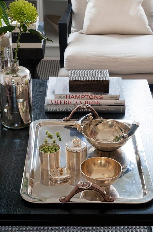 På soffbordet en mönstrad träask Chevron och en silverskål med hornhandtag, allt från K & co, silvervaser och bricka frånSlettvoll, silverskålar och burkar från Oscar & Clothilde.