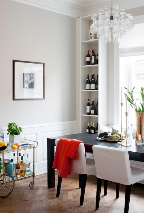 Matbordet är måttbeställt från Snickis och har plats för åtta personer. Stolar från Ikea, kökssoffan är platsbyggd liksom två hyllor på vardera sidan. Soffdynor, In your dreams, tyg från Frank & cordinata/ K&co, mönstrad linnekudde från K&co. På bordet mässingsljusstakar från Skultuna. Lampa från Designtorget.