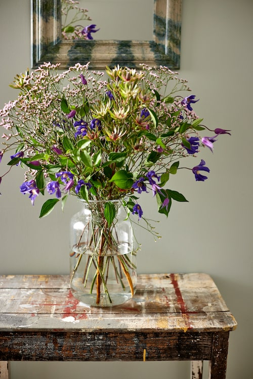 Blomsterfång med bland annat tistlar och blå klematis, i glasvas, 1100kr, Walles & Walles, litet målat bord, 1 500kr, Evensen antik, spegel, 4995 kr, Oscar & Clothilde.