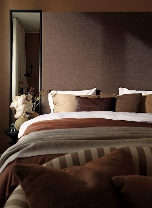 Den höga sänggaveln i brunt ylletyg är Elysée från Slettvoll, varifrån även torson kommer. Bäddset från Zara home, brunt överkast från Ohlssons tyger. Kuddarna på sängen från Zara Home och Hemtex.