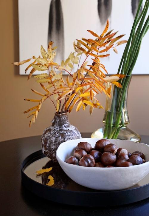 """Lägenhetens eleganta anslag mjukas upp av höstliga rönnkvistar och kastanjer i taktil, """"icke-perfekt"""" keramik."""