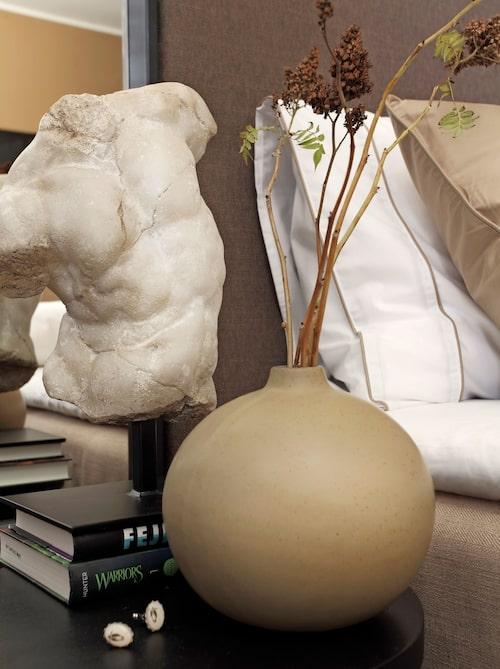 Ett arrangemang på sängbordet med liten keramikvas och torso från Slettvoll.