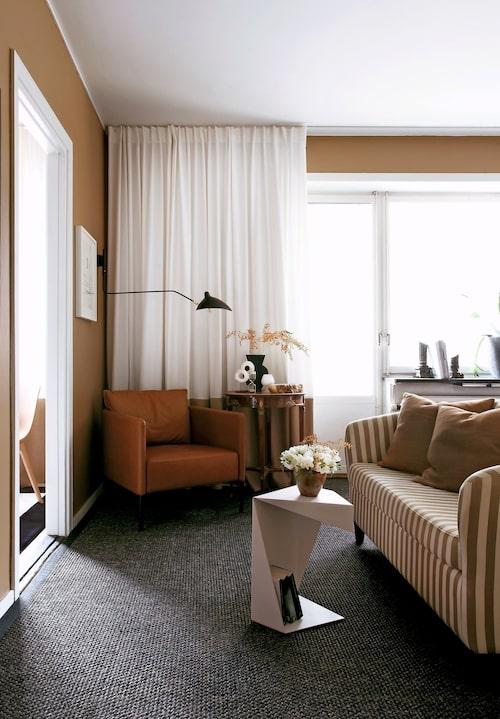 """En liten hörna för avkoppling. Den randiga soffan är ett secondhandfynd för 150 kronor. Färg, ränder och storlek passade perfekt. """"Den satte känslan i hela rummet"""" säger Geir Oterkjaer. Plåtbordet från Chilli har en origamikänsla som bryter av på ett kul sätt. Den konjaksfärgade läderfåtöljen är Piet från Slettvoll."""