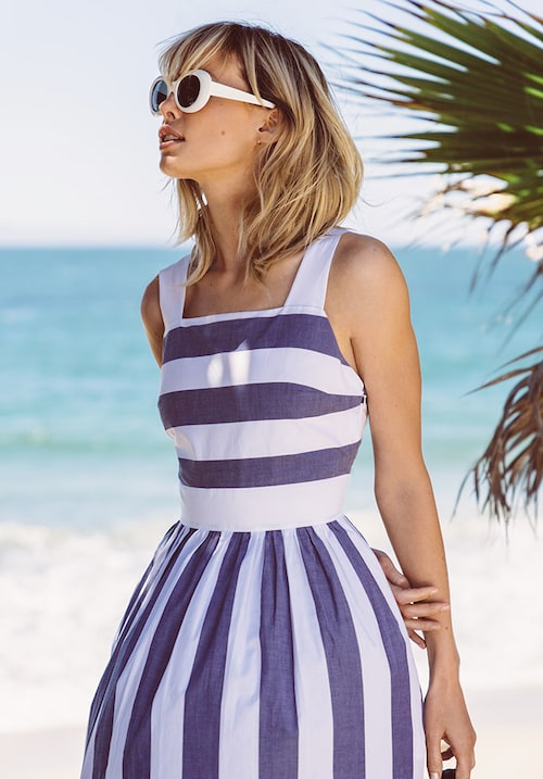 Blårandig vadlång klänning av bomull/elastan, stl 34–42, 799 kr, Cos. Ovala solglasögon av acetat, 2095 kr, Acne Studios. Örhängen, modellens privata.