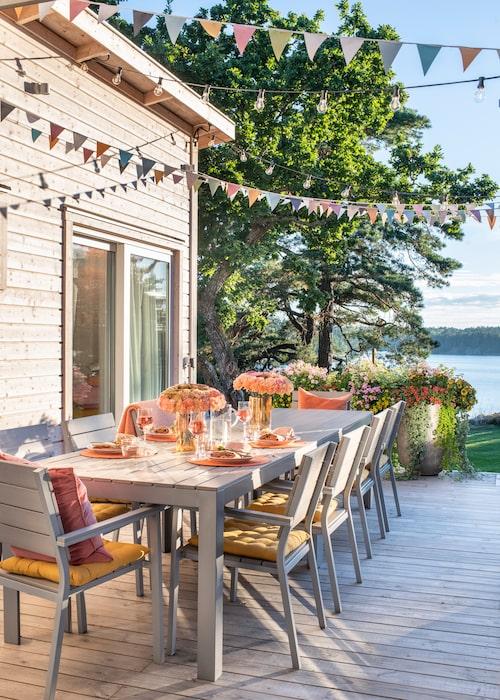 Altanen har vidunderlig utsikt över havsviken, med en gammal ek och väderbitna tallar som vindskydd. Trädäcket i impregnerat lärkträ är sammetslent och stickfritt att gå på. De stora betongkrukorna har fyllts med petunior, femtunga och härligt kvällsdoftande tobaksblommor i favoritfärgerna rosa, orange och gult. Bord och stolar är från Ikea, de är Pers utomhusklenoder som inte längre finns i produktion. De gula bomullsdynorna är från Ellos och pläden från Klippan. Vimplarna är köpta på Lagerhaus.