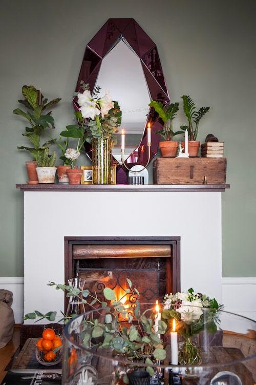 Den öppna spisen är dekorerad med en mängd växter i varierade krukor, ljus och färska blommor.