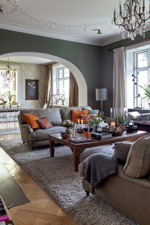 Skinande vita karmar och listverk bildar kontrast mot väggarna. För att skapa spänning och liv har Maja och Ole inrett i en modern, avspänd stil som bryter av mot de fina gamla detaljerna. En stor grå soffa från Lissoni piggas upp med orange kuddar.