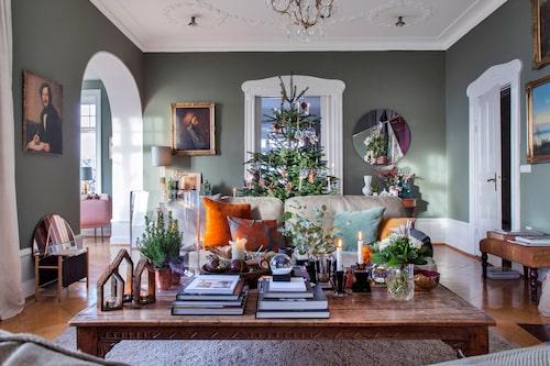 Den mörkgröna färgen i vardagsrummet ramar in julen perfekt. Klassiska howardsoffor från Parker Knoll och ett soffbord från Indiska. Bordet var ursprungligen ett matbord, men Ole kapade benen på det, och vips, hade de ett soffbord i rätt höjd.
