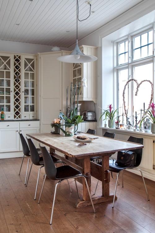 I väntan på maten kan man slå sig ner runt det gamla bockbordet. Det platsbyggda lantköket passar huset och stilen som hand i handske.