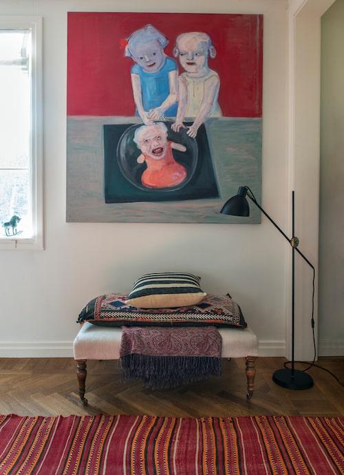 Målningen av Lena Cronqvist är knappast någon bakgrundskonst. På ottomanen ligger kelimkuddar och på golvet en kelimmatta i varma färger.