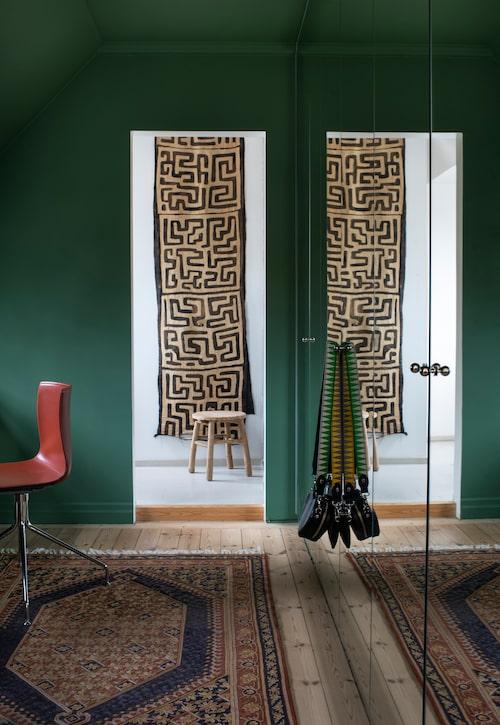 Garderobsrummet har fått mörkt gröna väggar och spegeldörrar. På golvet en handbroderad matta från Indien. Carolines väskor med hajtandsmönstrad axelrem finns att köpa på getthegallop.com. Bakom dörröppningen skymtar badrummet med en kenyansk matta på väggen.