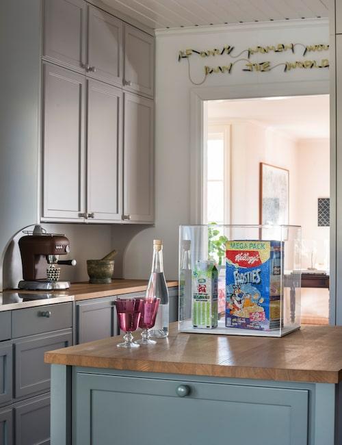 """På köksön ett konstverk av Estrid Åkermark i form av ett Kellogg's-paket och en mjölkförpackning – båda övertäckta med strass. Ovanför dörröppningen ett neonkonstverk av Josefin Eklund: """"If only women could rule the world""""."""