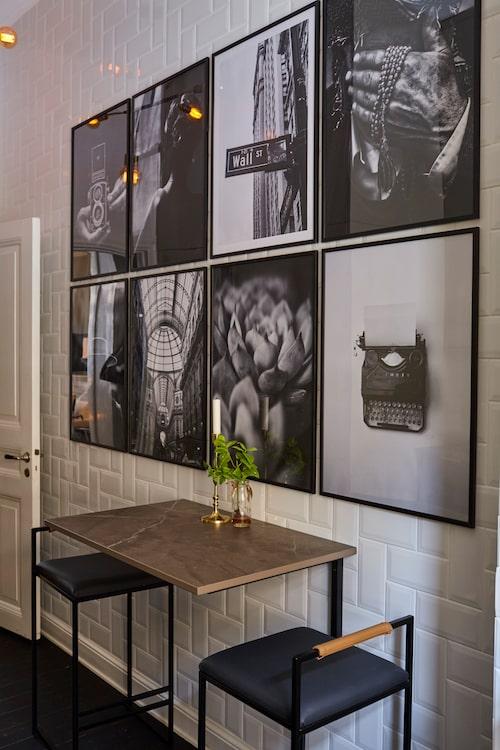 """Det vägghängda köksbordet är egen design. """"En smed fick göra fästena inunder, och så tog jag en spillbit marmor till bordsskivan."""" Stolarna, som Åsa älskar, kommer från By Crea. Svartvita foton, Papertown."""