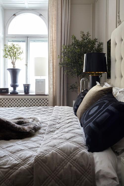 """Mixade textilkvaliteter i harmonisk färgskala i sovrummet.  Sängen från Ikea har fått egendesignad gavel, överkast från Mio och svarta kuddar, THerman. Gardinerna i linne är måttbeställda och kommer från Gotain. Konstväxter från Wexter. """"Sedan köper jag alltid färska snittblommor och sätter i en vas på bordet när vi är här."""""""