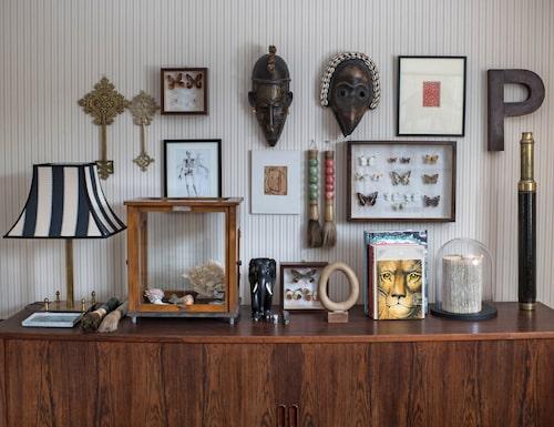 På det danska teakskåpet – som Pernilla ärvt från sin pappa – i arbetsrummet står allsköns artefakter som minner om resor, släktingar och loppisbesök. Lampskärm, Ralph Lauren.