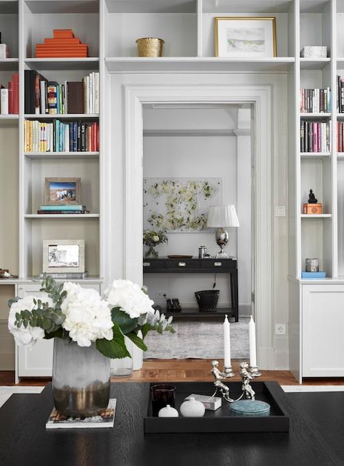 Platsbyggd bokhylla pryder vardagsrummet vägg.