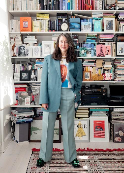 """""""Jag gillar gröna toner. Kavaj från Acne Studios, byxor från tidigare Céline och t-shirt från Weekday. Loafers från Prada, chunky länk från H&M:s tidigare samarbete med Moschino och bokstavshalsbandet från Céline. Vår överfulla bokhylla i bakgrunden."""