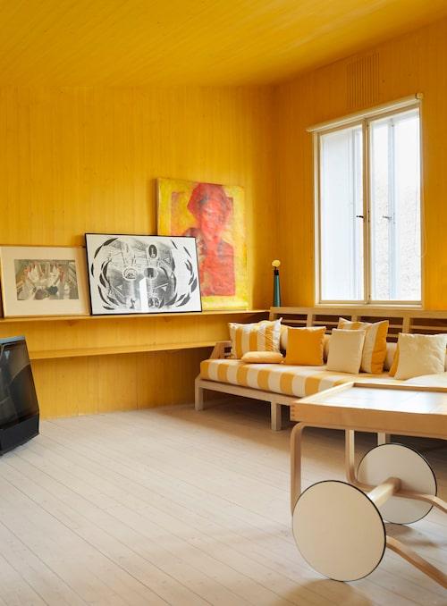 Det gula rummet var barnens del av huset på den tiden de bodde hemma. Tavlorna är målade av olika vänner. Serveringsvagnen är formgiven av Alvar Aalto, 30-tal.