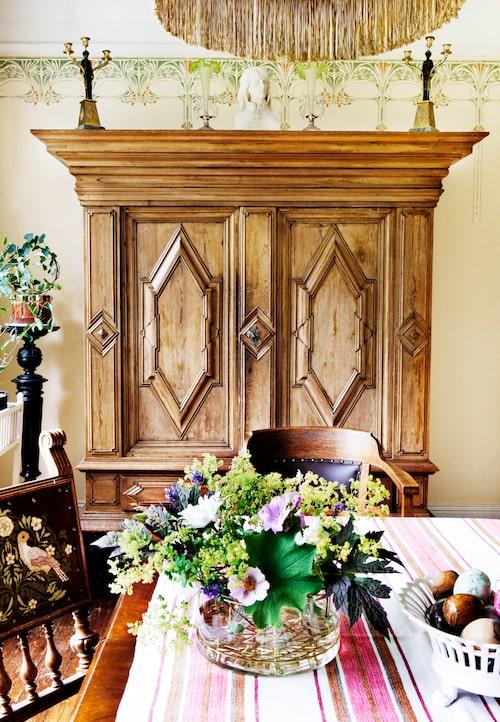 Väggarna runt matplatsen har schablonmålats av skickliga dekormålare. Det stora fina barockskåpet vid matplatsen ville ingen i släkten ha, så Fredrik och Kerstin tog hand om det. Kerstin har broderat stolsryggarna på matsalsstolarna med inspiration från William Morris.