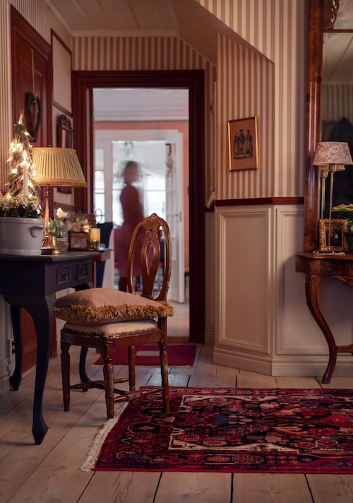 Hallen med vy mot tv-rummet. Spegeln i nyrokoko är från sent 1800-tal och lampan i mässing med mönstrad skärm kommer från Laura Ashley.