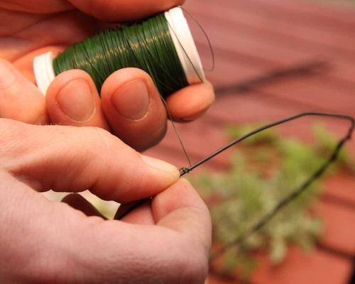 Börja med att göra kransens stomme av en böjlig metalltråd. Därefter fäster du den tråd du tänker använda för att binda fast dina blommor och blad med.