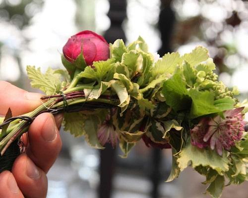 Fortsätt bygga din krans med knippe efter knippe och vinkla blommorna snett utåt. Lämna insidan utan växter men glöm inte sidorna.