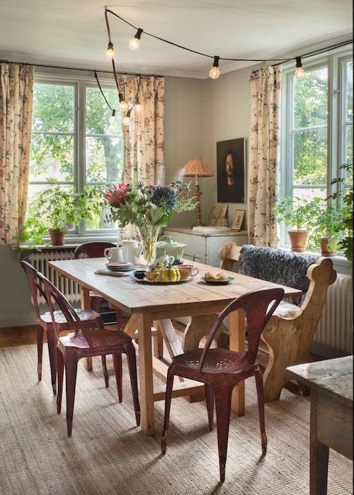 Matrummet intill köket har gårdssnickrat bord, vintagestolar av Joseph Mathieu och en kyrkbänk från Metropol auktioner. Gardinerna sydde Sofia av ett tyg med 1700-talsmönster, framtaget av Lars Sjöberg för Ljungbergs. Ljusslinga, Granit, sisalmatta, Ikea.