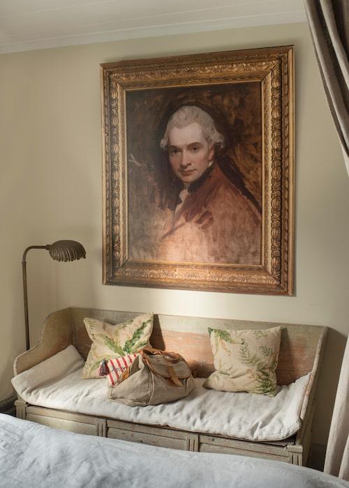 """Sofias och Brunos enda målning från Sotheby's: ett ofärdigt självporträtt av engelska porträttmålaren George Romney från cirka 1770, men det är bara en reproduktion av tavlan med ram och allt. """"Den hängde i skylten till Sotheby's i London när jag jobbade där och jag fick den när auktionen var över."""" Gustaviansk trågsoffa med sittdyna i linne, Garbo."""