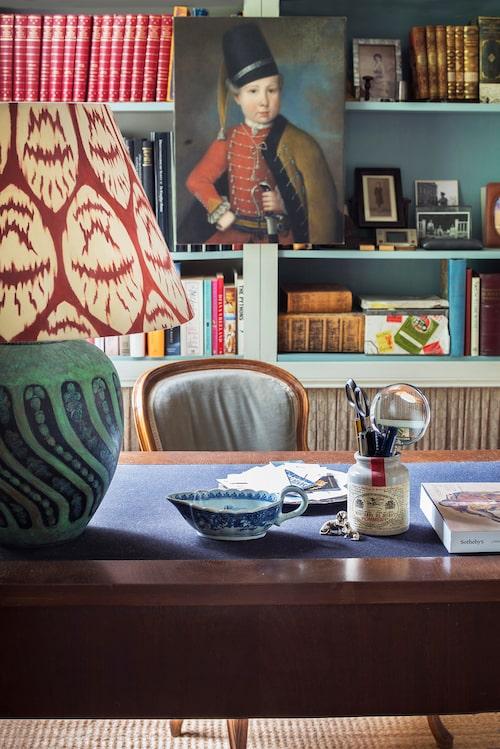 Pojken i husaruniform lade Bruno bud på, men priset for iväg så han målade av motivet från auktionskatalogen. Även lampan – från Ikea – har Bruno målat på, både fot och skärm. Ikeas Billybokhyllor har snofsats upp med grå lister, färg invändigt och linnegardin nertill. Böckerna i röda band är Svenska slott och herresäten.
