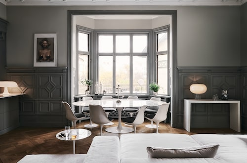 """Lovisa och Johan har hittills lyckats """"skramla ihop"""" fyra av Saarinens Tulipbord. Och åtta dito stolar, men de är ute efter tio. De köper på auktioner och Blocket. Öjusstake på bordet, Klong. I fönstret försilvrade krukor och vattenkanna från Skultuna. Till höger sideboard Quaderna, Zanotta, lampa, Foscarini, figur, Kaws."""