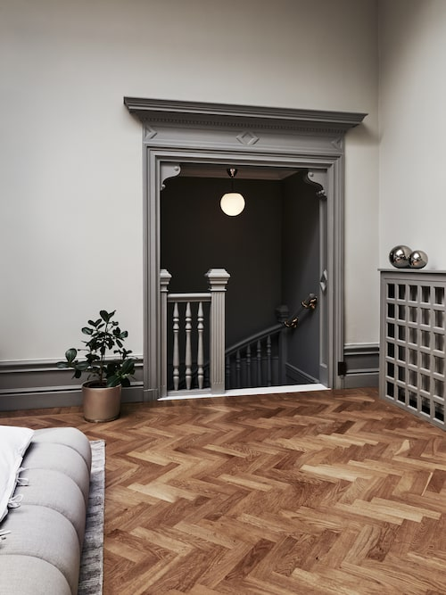 Trappan leder ned till hallen. Taklampa från Ikea. På elementskydden ett par dekorativa kulor från H&M Home. Kruka, Isadeco.