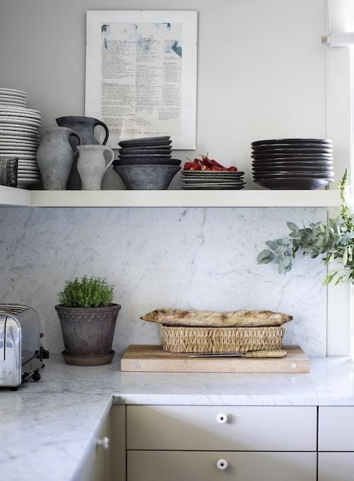Överskåp skulle ge ett för tungt intryck, ansåg familjen, så det blev öppna hyllor i köket och draglådor att stuva in allt i under bänken. Den gråblå keramiken på hyllan är från keramikern Bissa G Segerson.