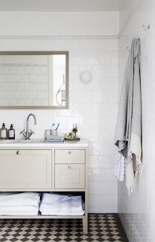 Det ena av lägenhetens två badrum. Badrumsbänken och spegeln är specialritade av Sundberg arkitekter, kakel från Gysinge, klinkers från Olde english tiles.