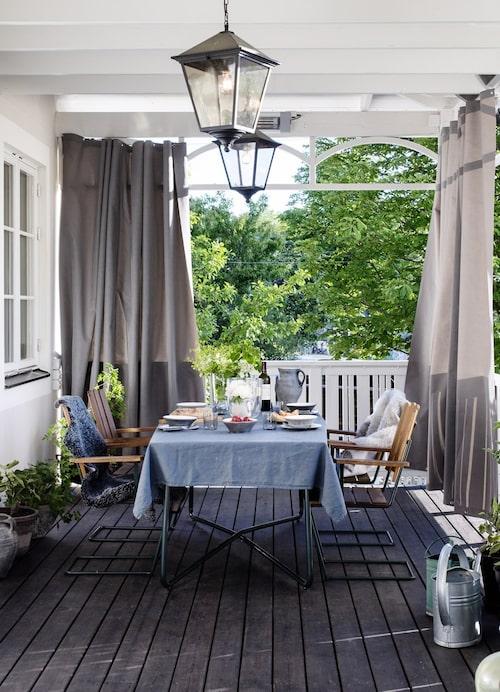 """Svartlaserat golv på den grönskande verandan. """"En underbar plats. Gardinerna runt om räcket förlänger säsongen"""", säger Gunilla. Gardinerna är från Celmar Sweden."""