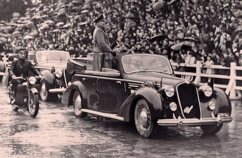 Benito Mussolini ståendes i baksätet på sin Alfa Romeo 6C 2300B från 1937.