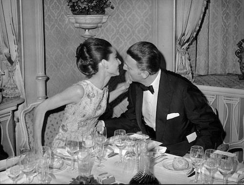 Paris 1964. Hubert de Givenchy viskar något i Audrey Hepburns öra under en middagsbjudning.