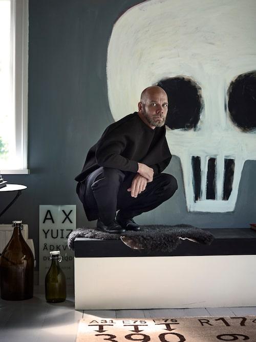 Konstnären Jan Håfström målade dödskallen direkt på väggen efter en blöt middag. Kenneths svarta dress – always black! – är från hans egen kollektion för By the no. Mattan är gjord av vännen Carouschka.