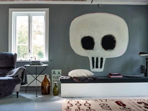 Hemtrevligt inbodd fåtölj och brukskonst (flaskor och optikertavla) blandad med coolare design (bordet och Carouschkas matta). Och vad vore rummet utan Jan Håfströms spontanmålade dödskalle?