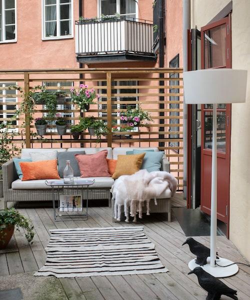 """Ett extrarum ute. Uteplatsen är hela 15 kvadratmeter. Soffan är från danska Cane-line och har hängt med länge. """"Det är värt att satsa på dyrare utemöbler. Här behöver man bara skaka av kuddarna om det regnar"""", säger Lotta. Golvlampan är från Spanien, mattan är vintage och brickbordet är från Maze. Svarta konstgjorda fåglar vakar över terrassen."""